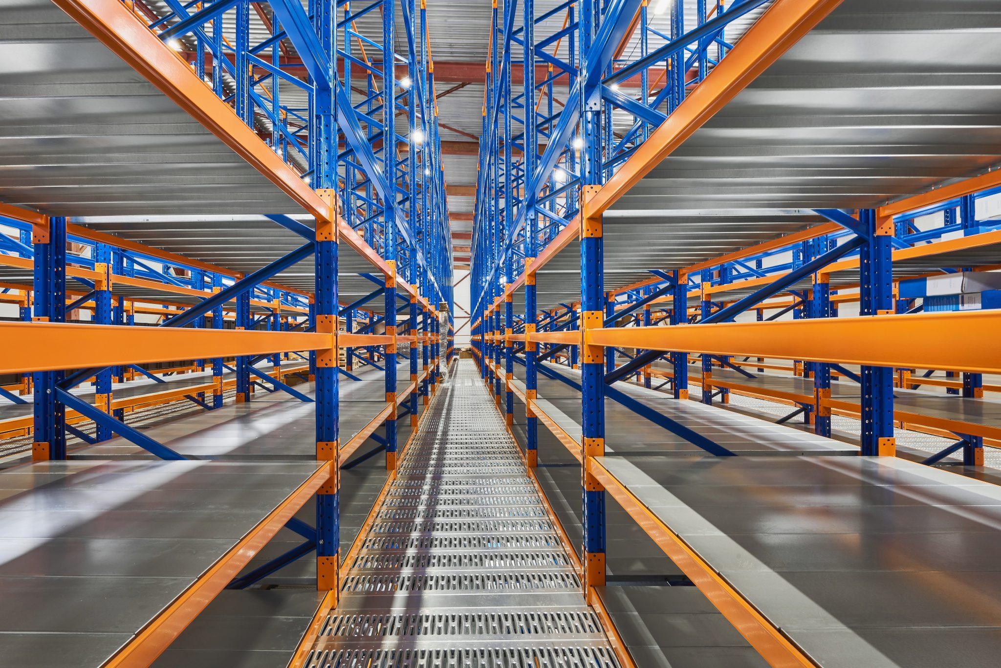Empty shelves in new distribution warehouse. Metal equipment for storage, racks blue orange, pallet racking system
